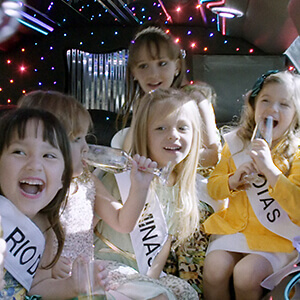 Child beauty contestants sit in a limousine