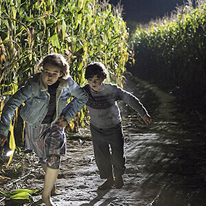 Regan and Marcus Abbott run from the monsters through their corn field