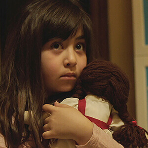 Dorsa clutches her doll